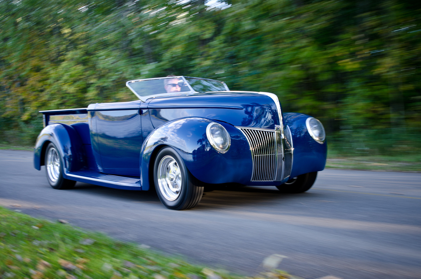 a blue roadster car driving through a forested area.