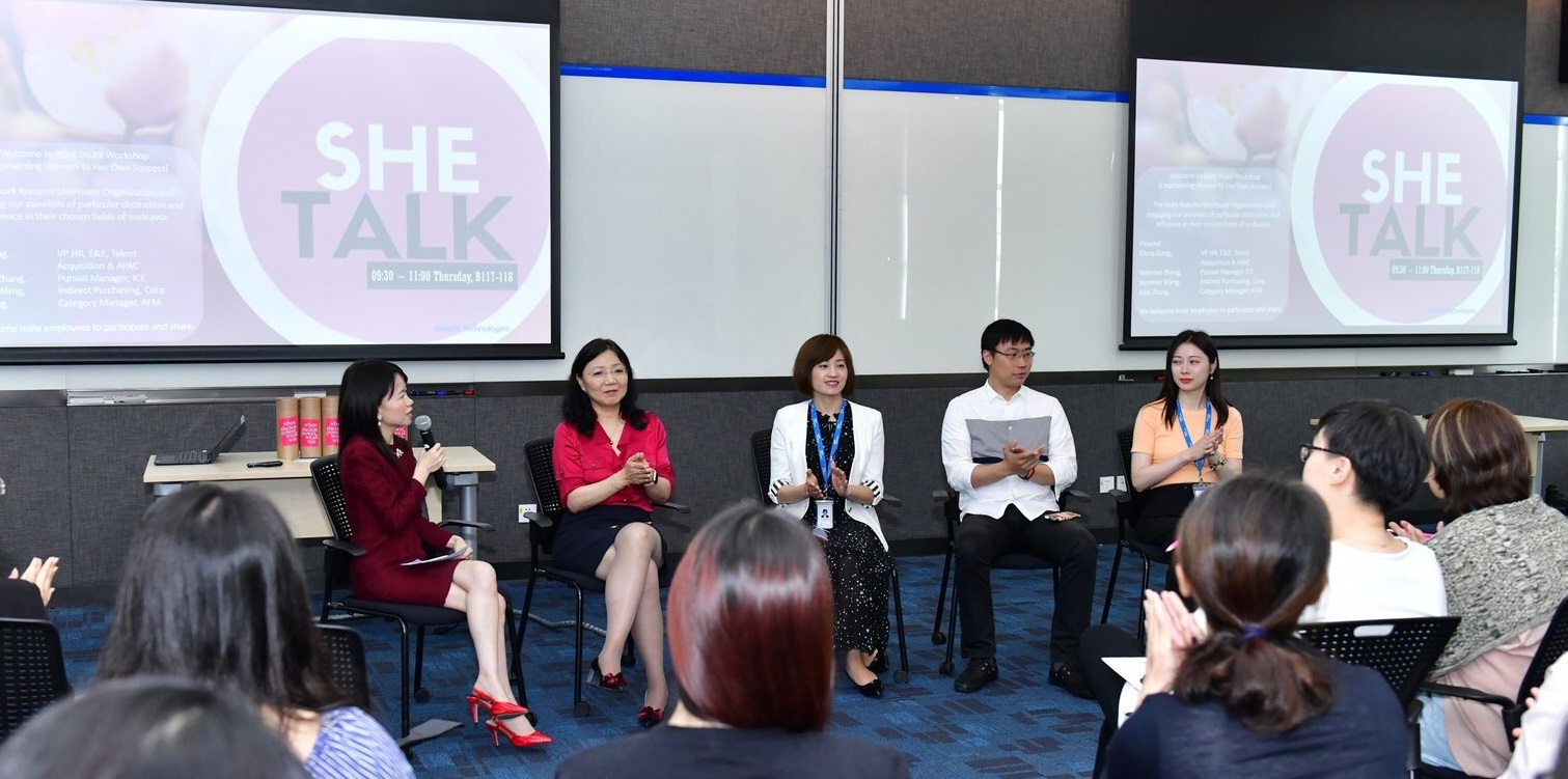 a group of executives participate in a panel discussion.