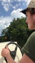 young adult male driving a boat for fishing