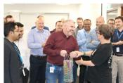 Man in red shirt accepts gift in shiny package with a laugh surrounded by smiling people.