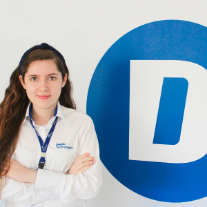 photo of woman wearing white delphi technologies windbreaker with delphi technologies lanyard smirking with crossed arms in front of large blue circle with D in middle affixed to wall in background