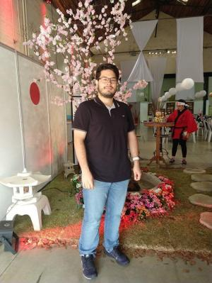 Young adult male posing in front of a cherry blossom tree inside an event show.