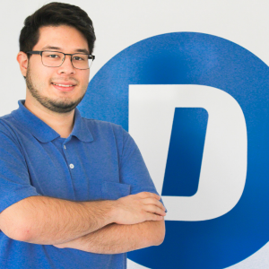 photo of man with dark hair wearing glasses and arms crossed smiling in front of large D on wall