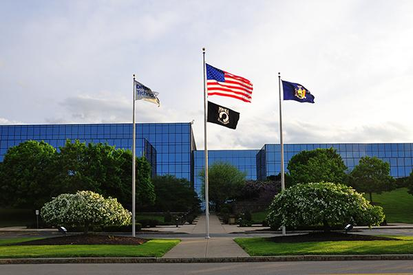 large, all-glass modern office building with flags flying at entrance