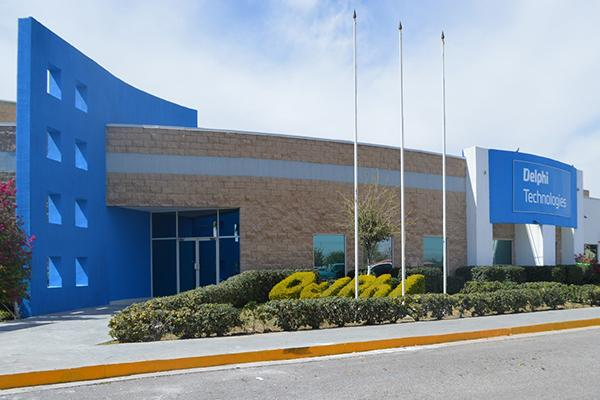 front entrance to large manufacturing plant with blue decorative concrete wall and elaborate landscaping