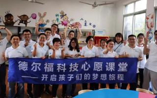 a group of people standing in a school library holding a banner.