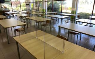 Cafeteria with glass partition walls on tables.
