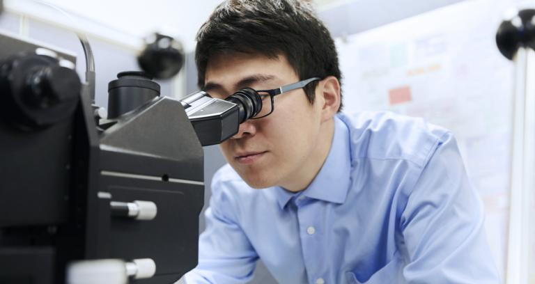 man wearing glasses looking through a microscope