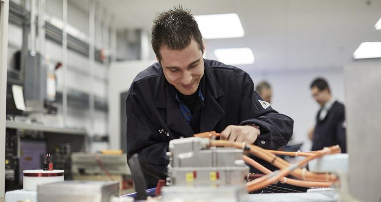 lab technician working at a table on advanced vehicle electronics