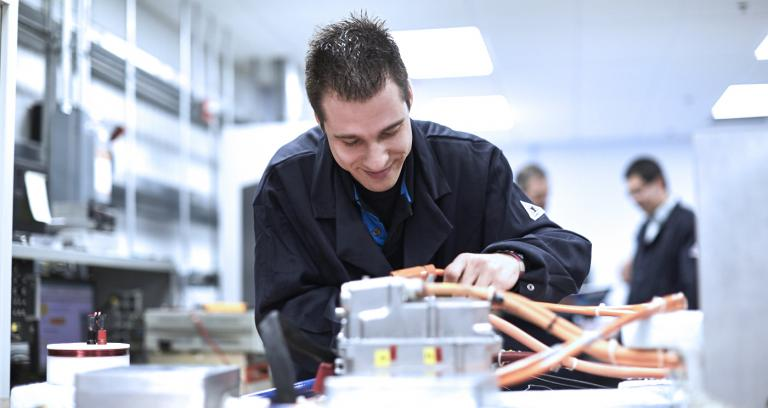 lab technician working on vehicle electronics products on a table