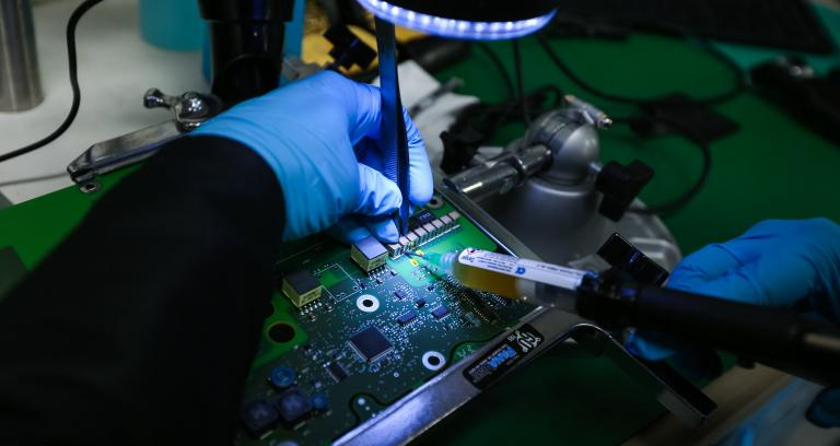 technician injecting fluid into circuit board during manufacturing process