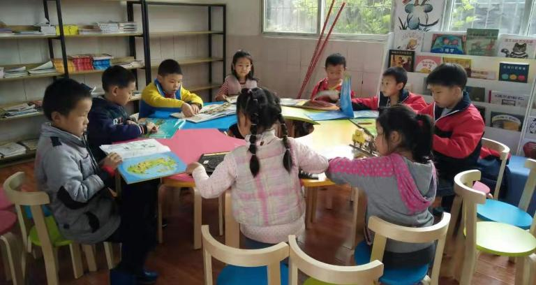 a group of young children reading gathered in a library.