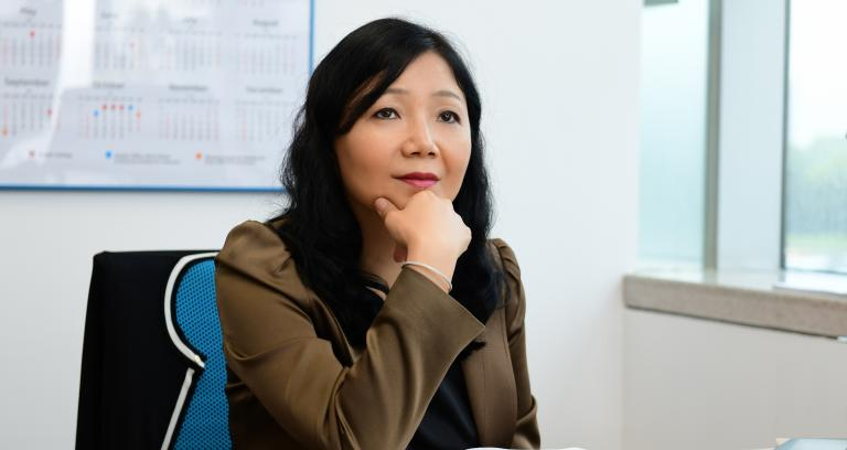 a professional businesswoman seated at desk looking into the distance.