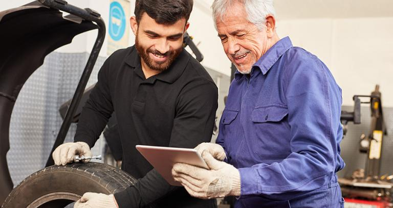 two auto mechanics looking at information on a tablet while repairing a vehicle.