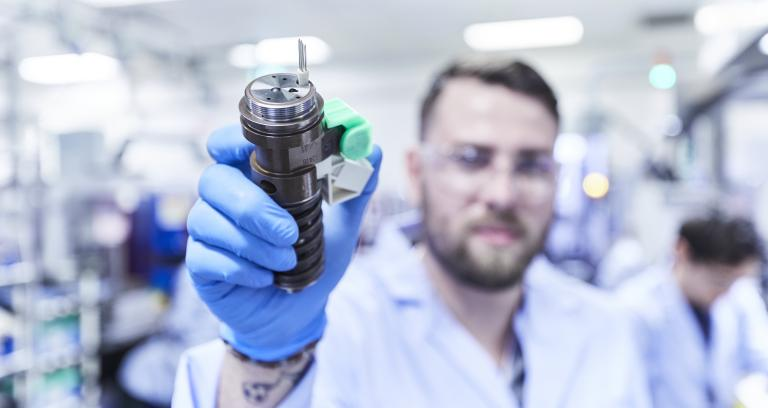 Man in lab coat holds up fuel injector