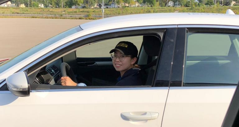 Woman in car smiles at the camera.