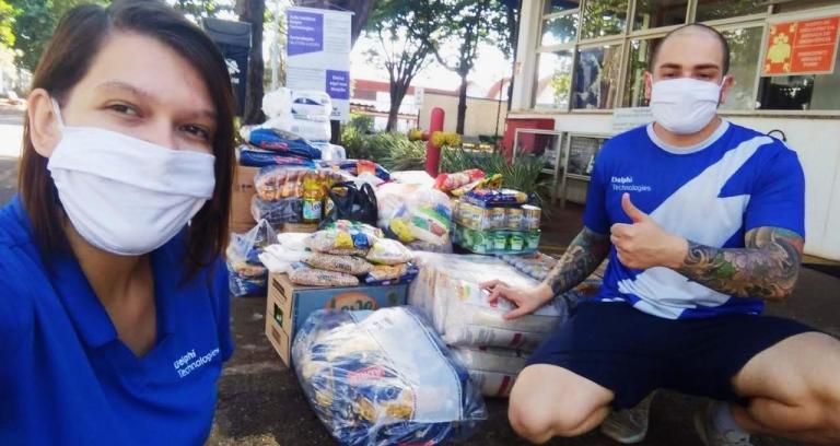 Women and man in masks and blue shirts pose in front of large pile of food and supplies