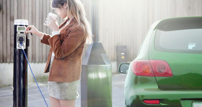 a woman recharging her green electric vehicle