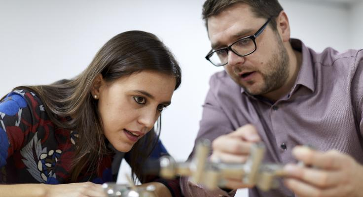 man and woman examining automotive components at a table
