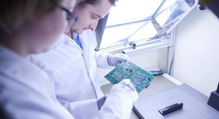 lab technicians viewing a circuit board