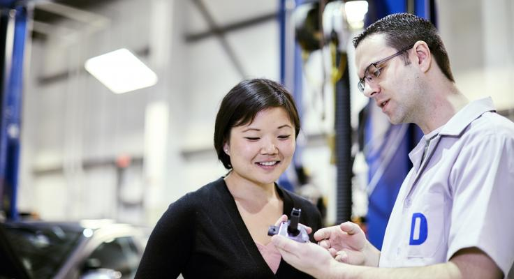Man and women discuss car part in lab setting.