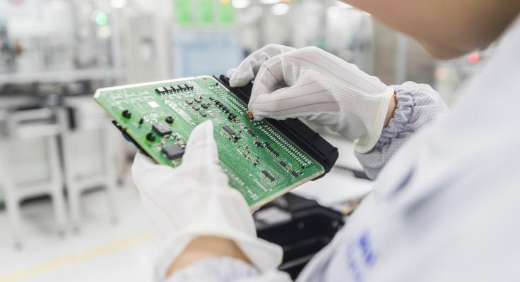 Close-up of a circuit board being held by lab tech in lab setting