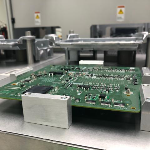 An electronic board sits on top of a table in a lab