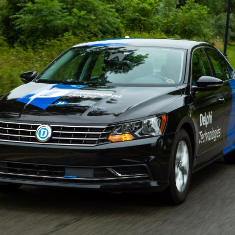 front view of a passenger car with company logos driving down a road.