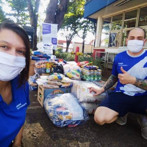 Man and woman pose in front of large pile of donation items