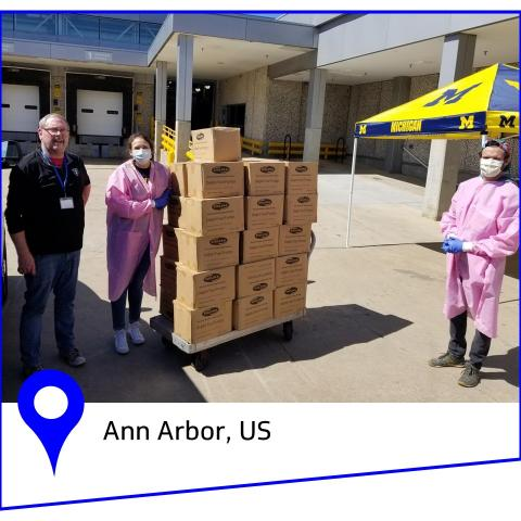 Three people stand in shipping zone with large cardboard boxes.