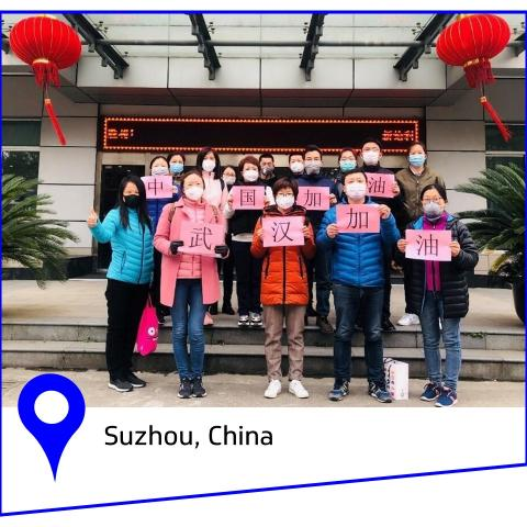 Group of women holding pink signs with Chinese symbols.