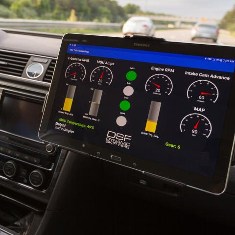 a driver behind the wheel of a car with a high-tech dashboard with special computer readouts on engine performance