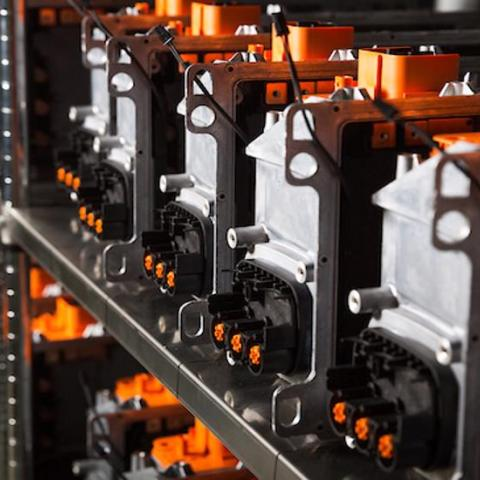 shelves stocked with automotive electronic components with bright orange connectors and switches.